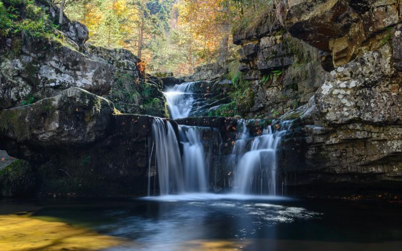 Cette chute d'eau au milieu des montagnes présente une image captivante