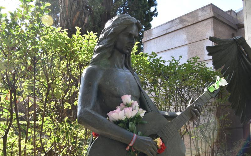 Sculpture d'Antonio Flores jouant de la guitare à côté du mausolée familial