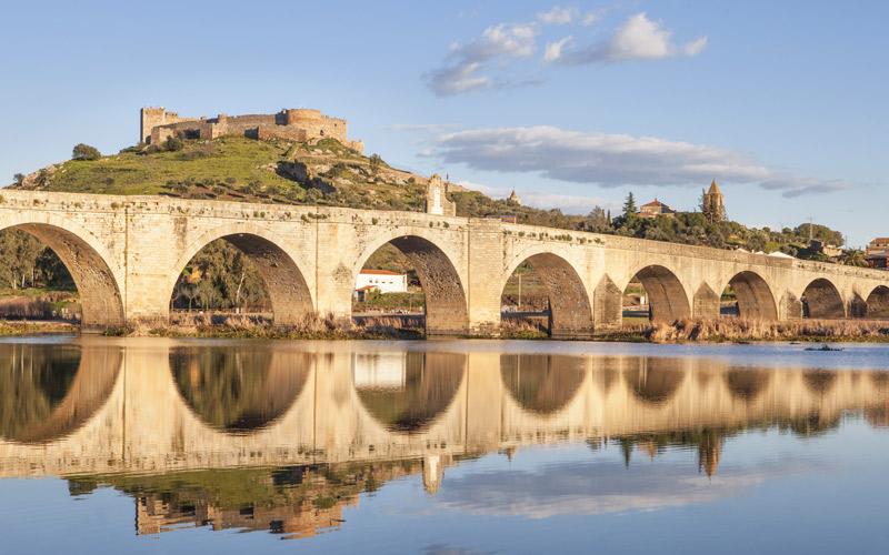 Pont romain reconstruit en 1630, puisque l'original se trouve sous les eaux du Guadiana. En arrière-plan, le château de Medellín en haut de la colline