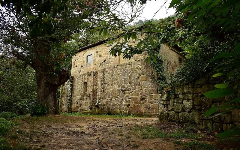 Mur du monastère de Santa Cristina s'élevant à travers les arbres