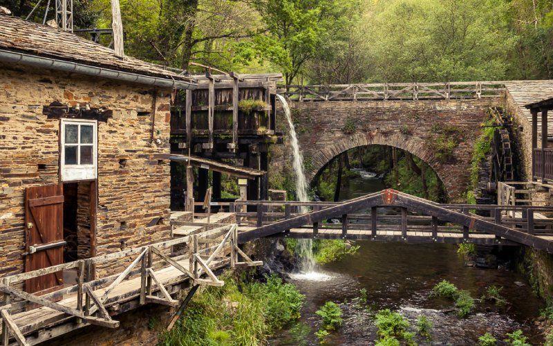 Un vieux moulin à eau au milieu de la montagne, entouré d'une végétation luxuriante, à Taramundi